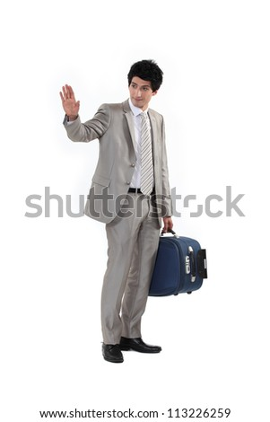 Man with suitcase waving goodbye - stock photo