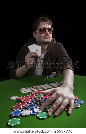 Man with sun glasses playing poker on green table. Chips and cards on the table. - stock photo