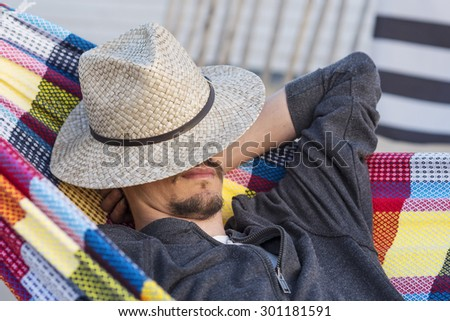 man with sun hat relaxing in a hammock at sunset - stock photo