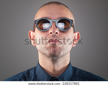 Man with sunglasses in a studio shot and looking up - stock photo