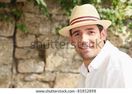 man with sunhat posing outdoors - stock photo