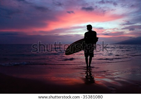 man with surfboard at sunset on tropical beach