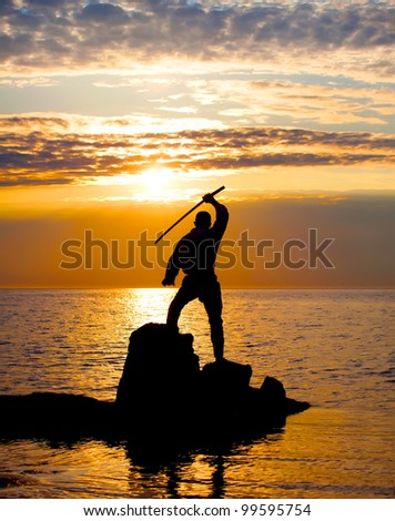 Man with sword near the sea at sunset time
