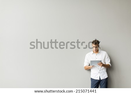 Man with tablet by the wall - stock photo