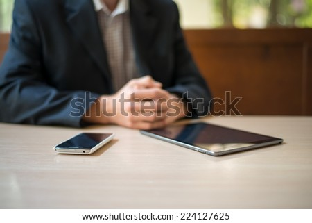 Man with tablet computer reading news at motning in cafe - stock photo