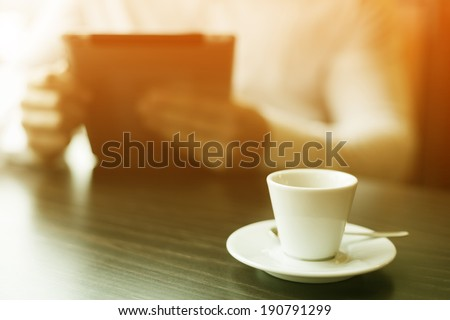 Man with tablet computer reading news at motning in cafe shop - stock photo