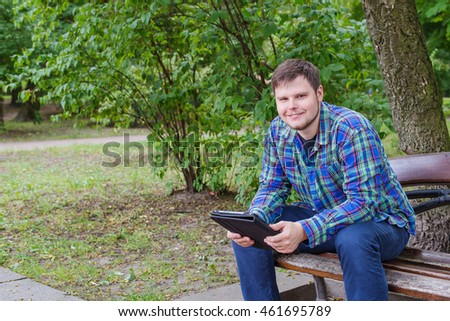man with tablet on a bench