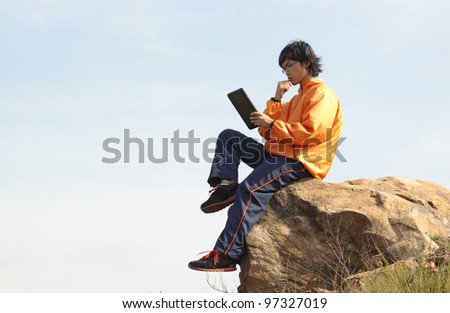 man with tablet outdoor at day