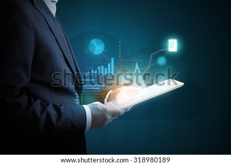 man with tablet pc analyzing virtual diagrams of financial activity over dark background - stock photo