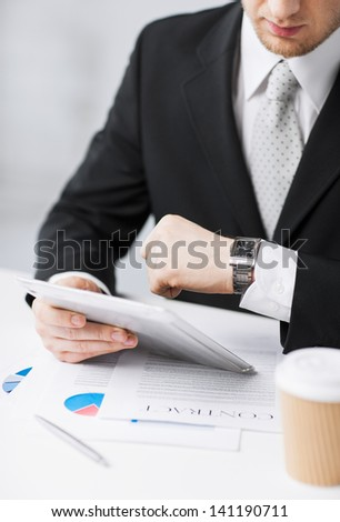 man with tablet pc and cup of coffee looking at watch - stock photo