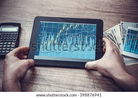 man with tablet pc, forex chart  on desk. toned image - stock photo