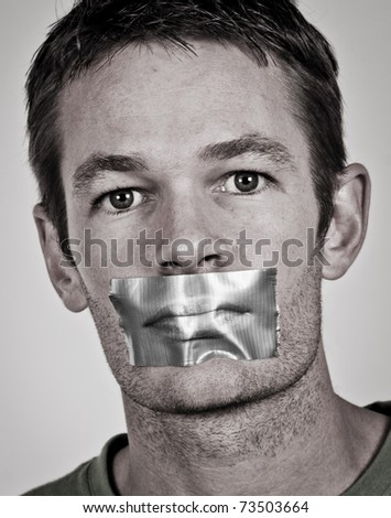 Man with tape over his lips - stock photo