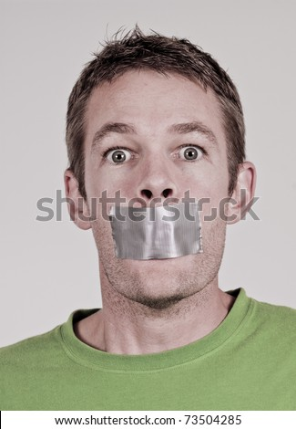Man with tape over his mouth - stock photo