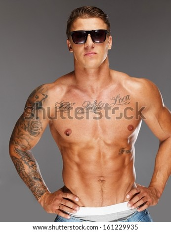 Man with tattooed muscular torso in blue jeans - stock photo