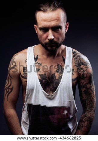 man with tattooes on his arms. Silhouette of muscular body. caucasian brutal hipster guy  modern haircut, looking like criminal