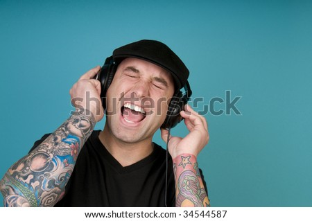 Man with tattoos listening to headphones and singing
