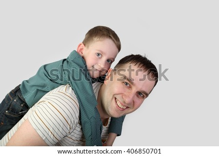 Man with teenage boy on back happy smiles on gray background - stock photo