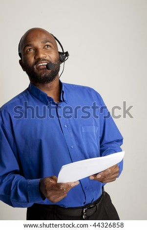 Man with telephone headset and documents conducting business.