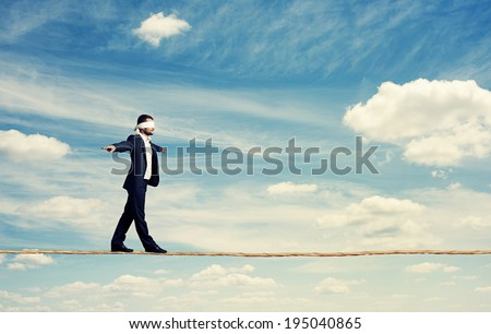 man with the blindfold walking on the rope over blue sky - stock photo