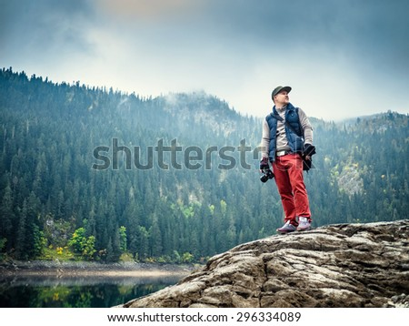 Man with the camera at the lake - stock photo