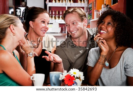 Man with three pretty women in coffee house - stock photo