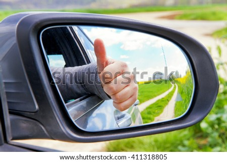 Man with thumb up in side mirror - stock photo