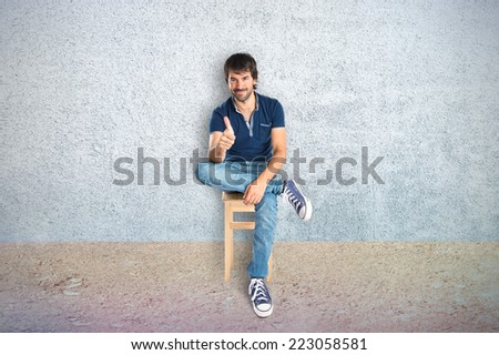 Man with thumb up over textured background