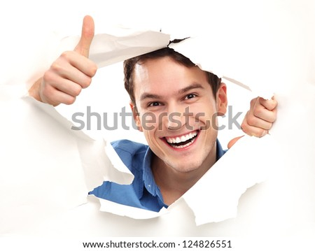 Man with thumbs up peeping through paper hole - stock photo