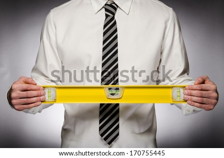 Man with tie holding a level - stock photo