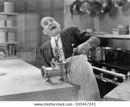 Man with tie stuck in meat grinder - stock photo