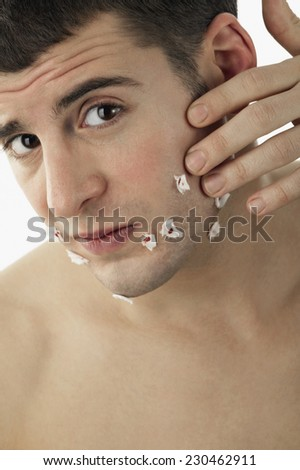 Man with Toilet Paper Stuck to Shaving Cuts - stock photo