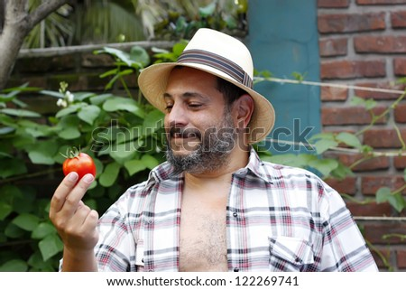 man with tomato in the garden - stock photo