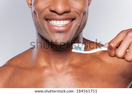 Man with tooth brush. Cropped image of young shirtless African man holding a toothbrush with toothpaste and smiling while standing against grey background - stock photo