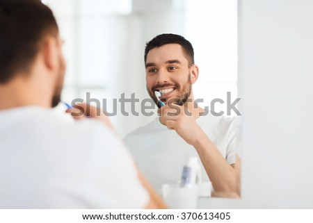 man with toothbrush cleaning teeth at bathroom - stock photo