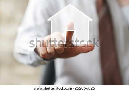 Man with touchscreen house icon web sign - stock photo