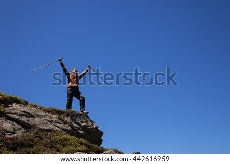Man with trekking poles standing on the top of the mountain