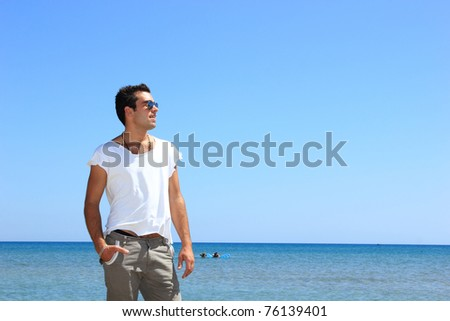 man with tshirt posing at the beach - stock photo