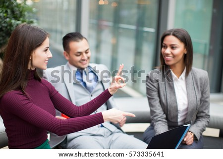 Man with two beautiful business women in office. One woman showing ok hand sign