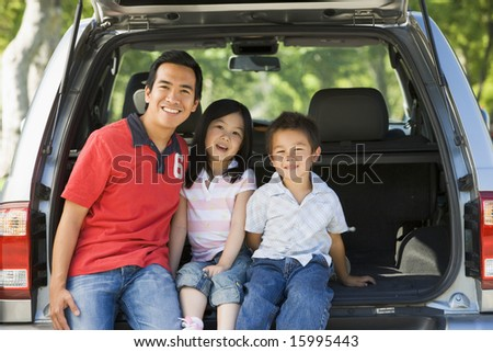 Man with two children sitting in back of van smiling