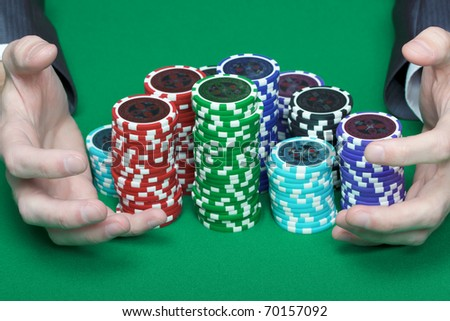 man with two hands rakes the pile of poker chips - stock photo