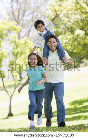 Man with two young children running outdoors smiling - stock photo