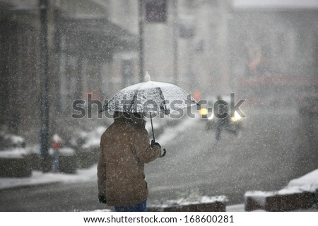 Man with umbrella during snow storm in the street - stock photo
