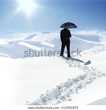 Man with umbrella on winter hill - stock photo