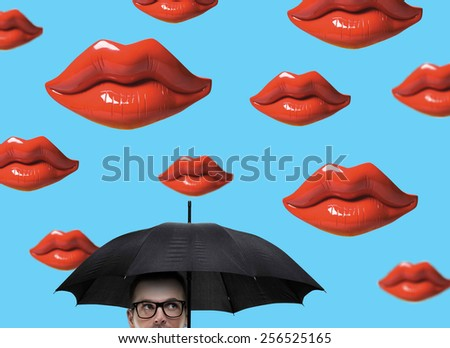 Man with umbrella under abstract flying giant lips - stock photo