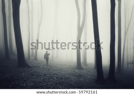 man with umbrella walking in a dark forest with fog and black trees - stock photo