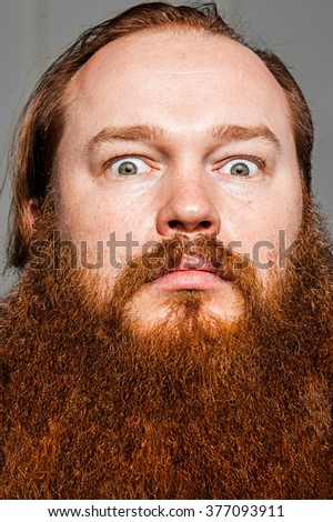 Man with uncombed messy beard staring at camera - stock photo
