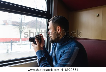 Man with vintage camera in the train. View from the window. - stock photo