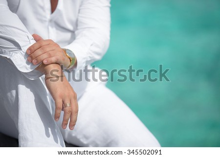 Man with watch in white dress sitting on background of turquoise water - stock photo