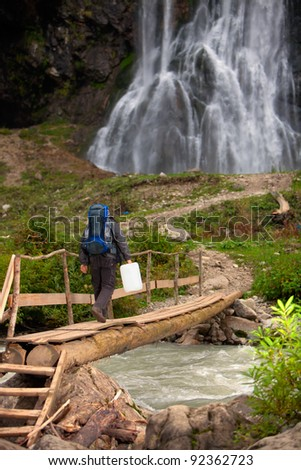 Man with water can  walking to waterfall