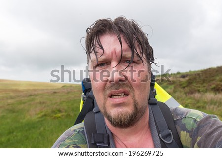Man with wet hair and sweaty face looking exhausted and challenged - stock photo